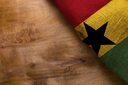 Three-color flag of Ghana on a wooden surface.