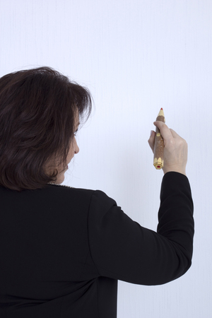 tailleur: Senior business woman with a pencil on a white background