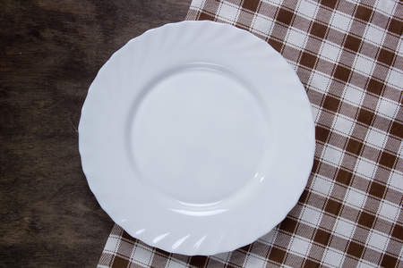 White dish on a wooden table and checkered napkin