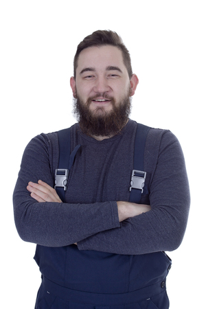 Portrait of happy handyman in overalls standing arms crossed over white backgound Stock Photo