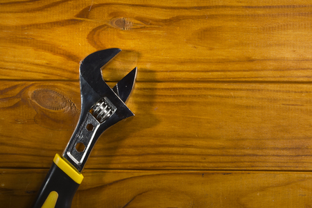 New adjustable wrench on a wooden background