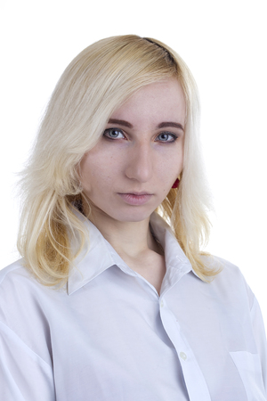 Portrait of a young sad blonde woman on a gray background