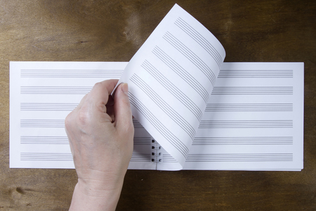 sheet of paper: Hand turns over the pages of a notebook on a wooden background Stock Photo
