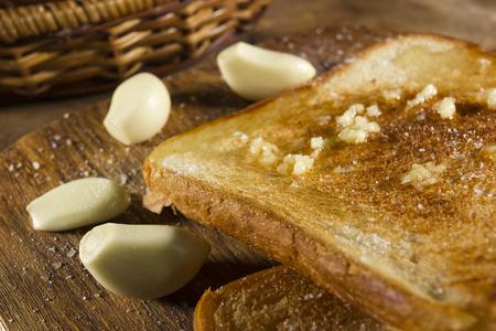Roasted garlic bread close-up, and cloves of fresh garlic Stock Photo