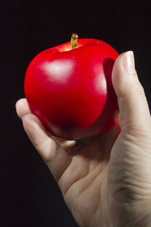 gloom: Red apple in hand on a black background