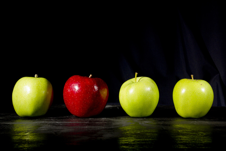 赤いリンゴ青リンゴの行に立って