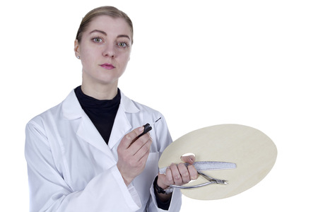 Young woman in a white coat with a manicure tool and a palette Фото со стока