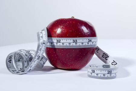 concept image of a tape measure around a red apple