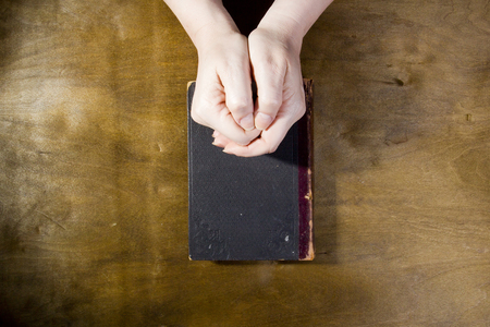 humility: Female hands in prayer with a book on a wooden background