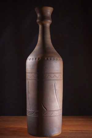 Clay bottle with wine on a wooden table