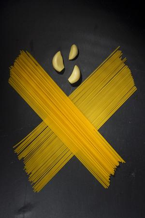 Macaroni and garlic on a black stone board Imagens