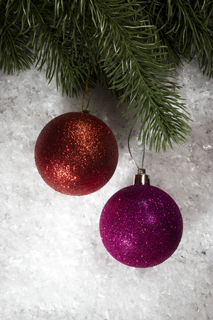 Multicolored balls and fir branch on snow Imagens