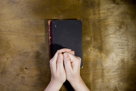 jehovah: Female hands in prayer with a book on a wooden background