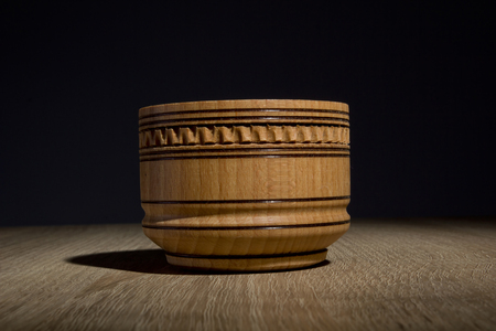 lacquer ware: Wooden tableware for salt on a table on a black background