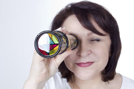 Adult woman looking into a kaleidoscope on a white background Standard-Bild