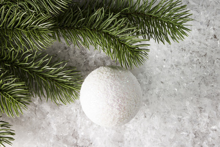 Branch of spruce with a New Years ball on white snow Banco de Imagens