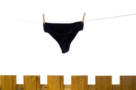Female underwear dries on a rope behind a fence