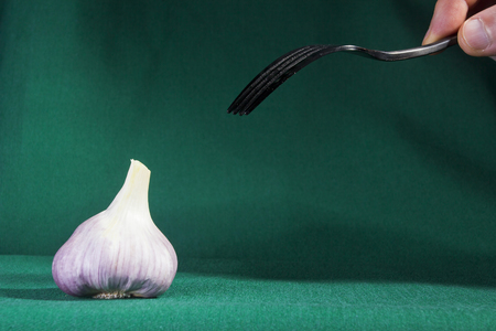 Fork and garlic on a green background Stok Fotoğraf