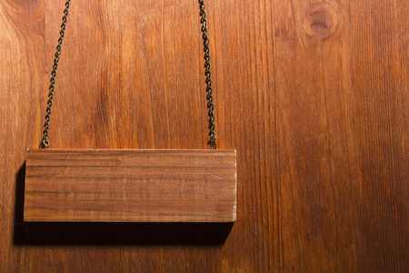 Wooden signboard on a chain on a wooden background Stock Photo