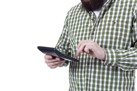 Young bearded man counts on a calculator against a white background