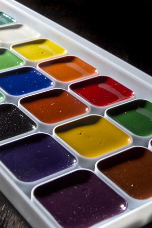 Multicolored watercolor paints in a white plastic box Stock Photo