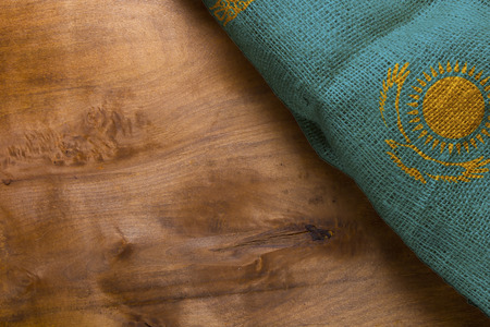 Flag of Kazakhstan from rough fabric on a wooden background.