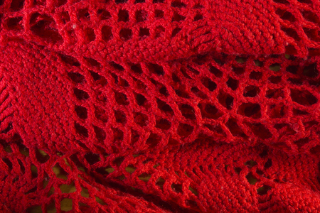 Red knitted shawl close-up in the form of a background Фото со стока