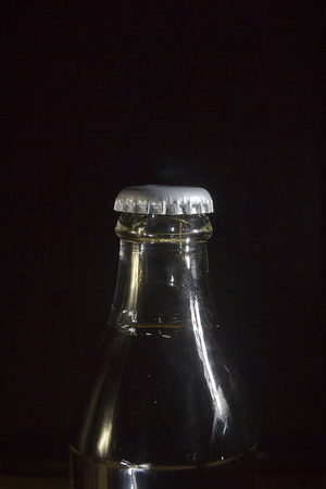 A neck of a cola bottle close-up on a black background