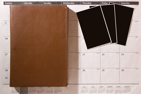 Three photos on an office calendar with an old leather-bound book