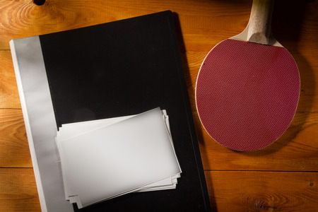 Folder with photos and tennis racket on a wooden table