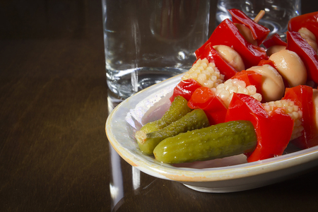 Pickles on skewers in porcelain ware on a reflective surface