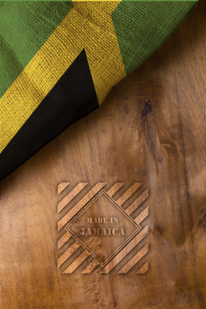 National flag of Jamaica from burlap. Wooden background.