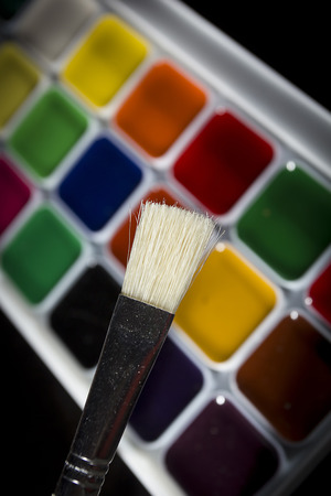 Multicolored watercolor paints in a white plastic box and tassels Stock Photo