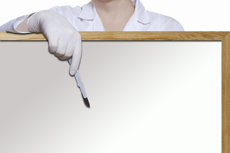 Hand of a female doctor with a scalpel on the background of a blackboard Reklamní fotografie