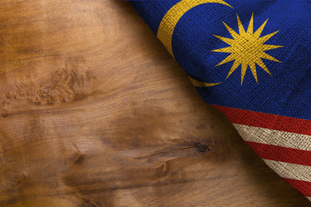 Flag of Malaysia from rough fabric on a wooden surface