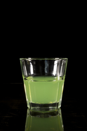 A glass with absinth on a black reflecting surface Фото со стока