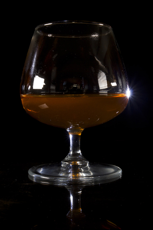 A glass of cognac on a black background on a reflective surface
