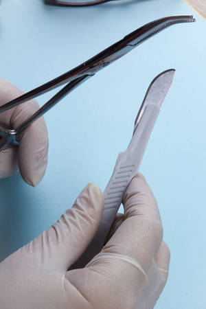 Hands in latex gloves with surgical instruments on a blue background