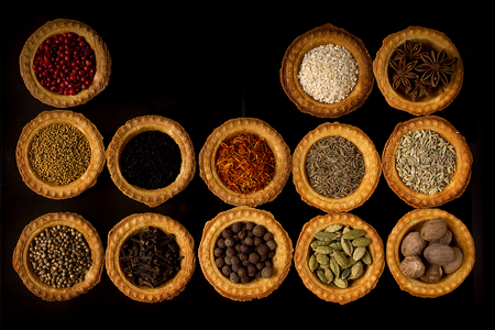 Tartlets with spices on a black background
