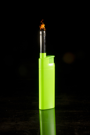 Green lighter on a black reflective surface 版權商用圖片