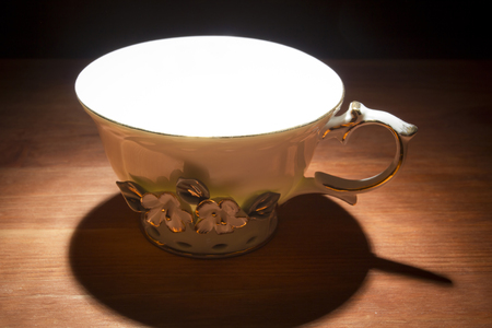 Empty white tea cup on a wooden table