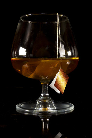Cognac glass with a bag of tea on a black background