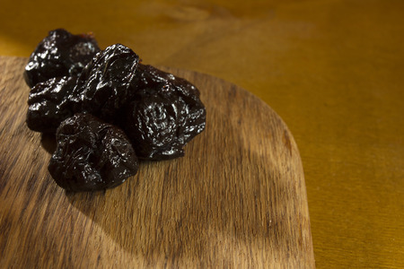Prunes, dried plums on a wooden table