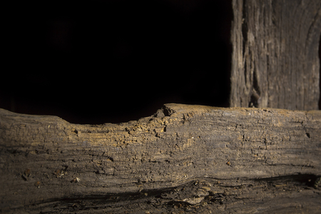 Old rotten logs stacked in crossbeams on a black background Archivio Fotografico