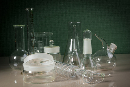 Laboratory glassware on the table on a green background Stok Fotoğraf