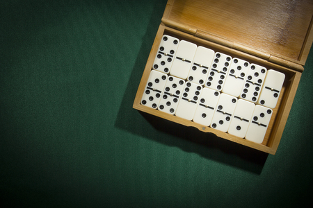 Dominoes in a wooden box on a green background
