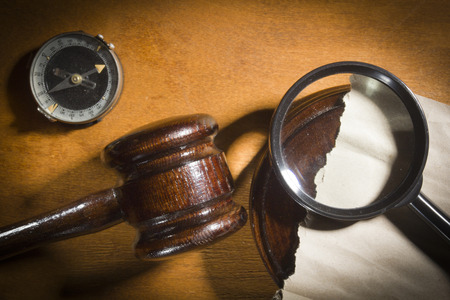 Judge's gavel and magnifier on a wooden table