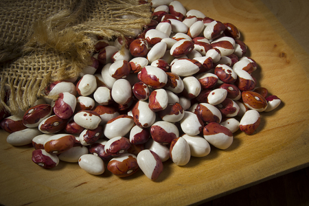 Beans in a wooden plate on a black background