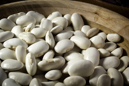 Beans in a wooden plate on the table Archivio Fotografico