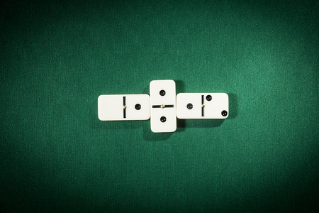 Stacks of Dominoes on a table covered with green cloth